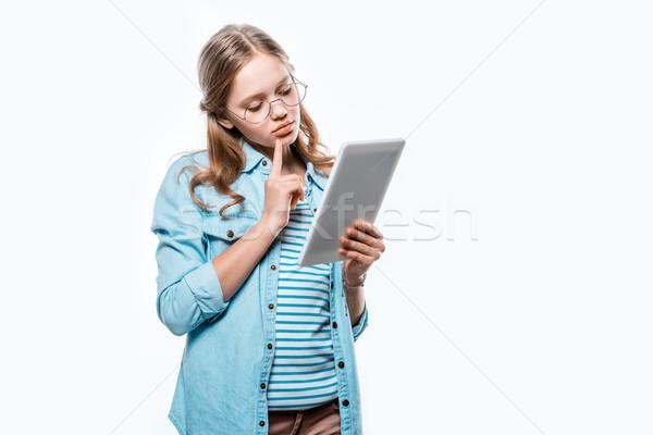 Töprengő tinilány szemüveg digitális tabletta izolált Stock fotó © LightFieldStudios