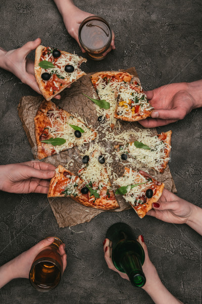 Close-up view of friends eating pizza on dark background Stock photo © LightFieldStudios