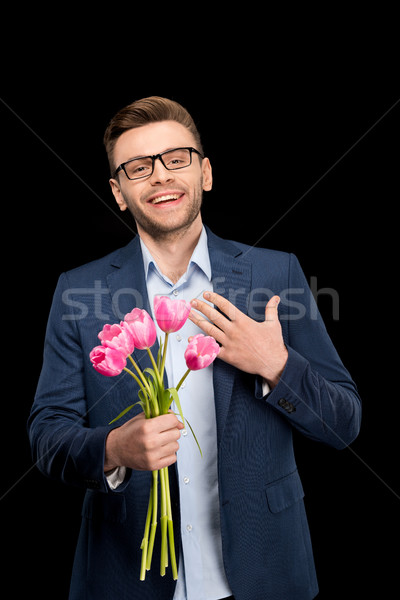 Happy young man in eyeglasses holding pink tulips on black, international womens day concept Stock photo © LightFieldStudios
