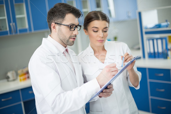side view of concentrated man and woman scientists writing in notepad in lab Stock photo © LightFieldStudios