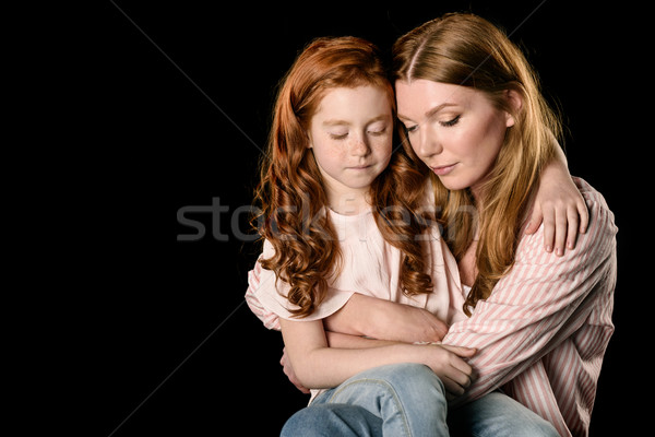 Beautiful mother and daughter sitting together and looking down isolated on black Stock photo © LightFieldStudios