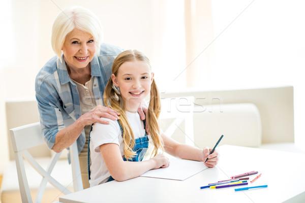 Beautiful girl and senior woman drawing together and smiling at camera  Stock photo © LightFieldStudios