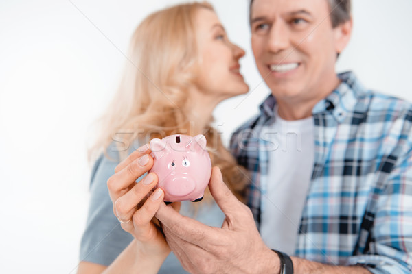 Front view of happy couple holding piggy bank on white Stock photo © LightFieldStudios
