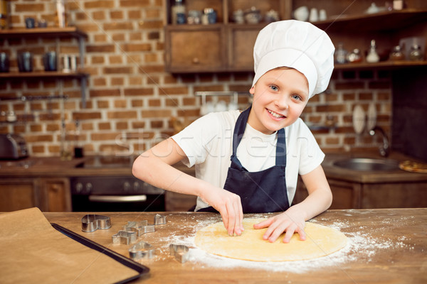 portrait of little boy in chef hat making shaped cookies in kitchen Stock photo © LightFieldStudios