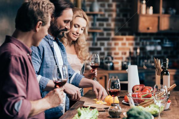 Freunde trinken Wein Kochen Abendessen Seitenansicht Stock foto © LightFieldStudios