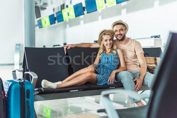 Pareja espera embarque aeropuerto sonriendo mirando Foto stock © LightFieldStudios