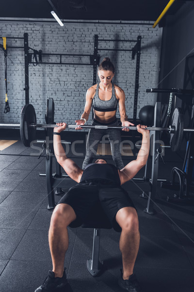 woman helping man to lift barbell Stock photo © LightFieldStudios