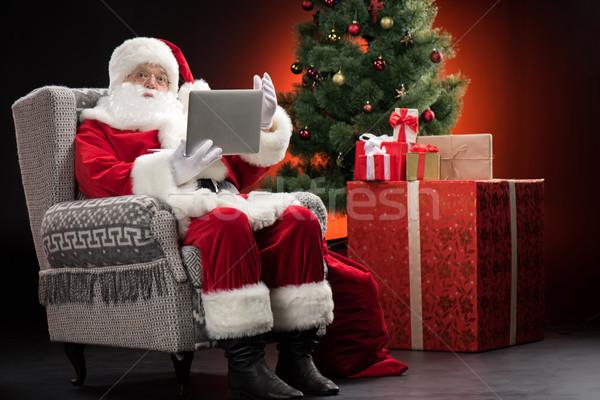 Santa Claus using laptop and gesturing Stock photo © LightFieldStudios