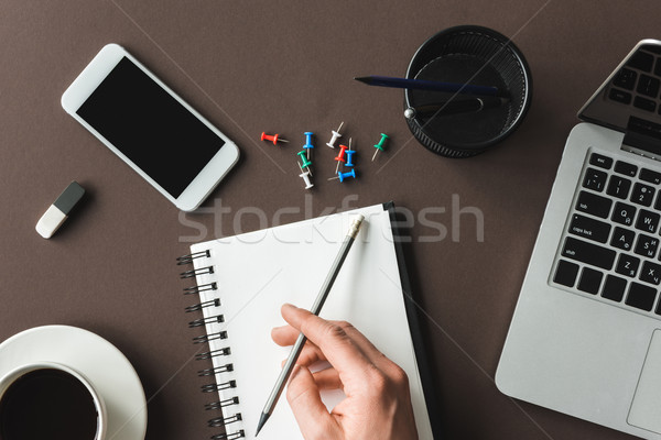 Close-up partial view of person holding pencil and writing in notebook at desk with laptop, smartpho Stock photo © LightFieldStudios