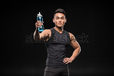 asian sportsman with sports bottle Stock photo © LightFieldStudios