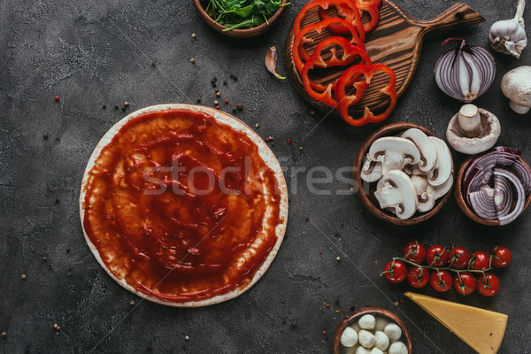 top view of pizza dough with ketchup and vegetables on concrete table Stock photo © LightFieldStudios