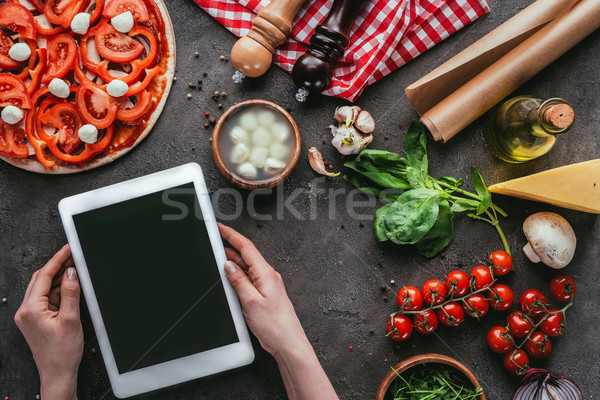 cropped shot of woman using tablet while preparing pizza on concrete table Stock photo © LightFieldStudios