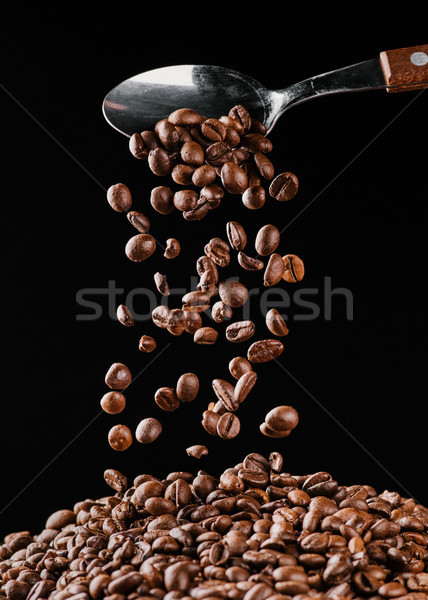 coffee beans falling from spoon on pile isolated on black Stock photo © LightFieldStudios