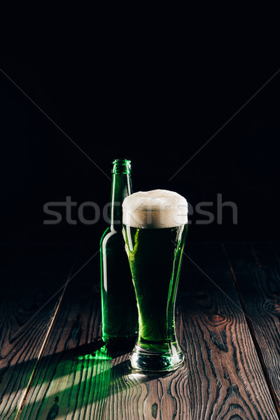 shining glass and bottle of green beer on wooden table, st patricks day concept Stock photo © LightFieldStudios