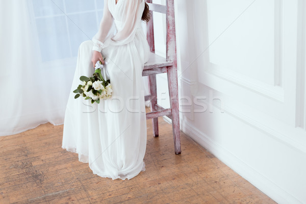 cropped view of elegant bride sitting on big chair with wedding bouquet Stock photo © LightFieldStudios