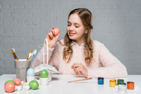 beautiful smiling teenage girl holding egg during preparation for easter Stock photo © LightFieldStudios