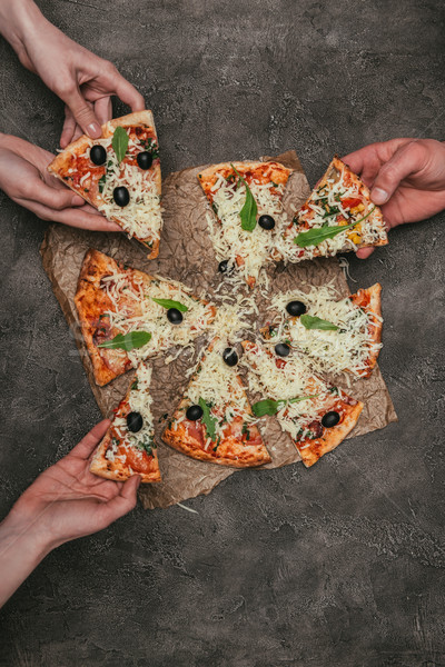 Close-up view of people eating pizza on dark background Stock photo © LightFieldStudios