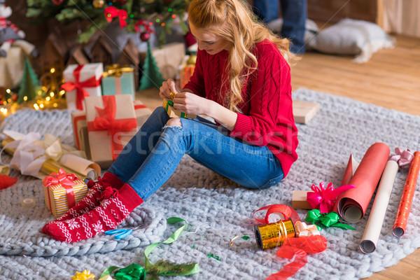 Girl wrapping gift box Stock photo © LightFieldStudios