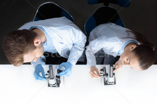 top view of scientists in uniforms working with microscopes in laboratory  Stock photo © LightFieldStudios