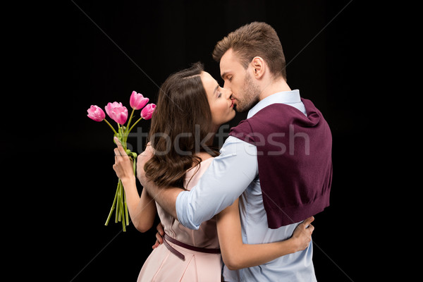 back view of man kissing woman with tulips bouquet on black, international womens day concept Stock photo © LightFieldStudios