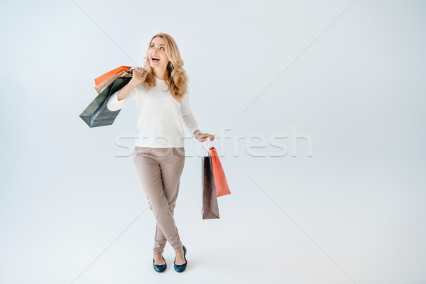 Excited beautiful woman holding shopping bags and looking up on grey Stock photo © LightFieldStudios