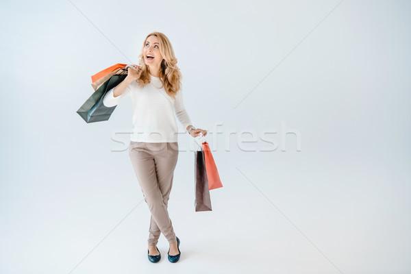 Izgatott gyönyörű nő tart bevásárlótáskák felfelé néz szürke Stock fotó © LightFieldStudios