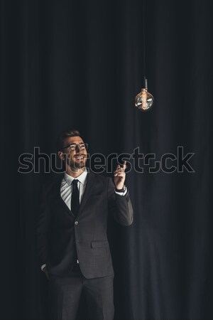 handsome businessman with lightbulb Stock photo © LightFieldStudios