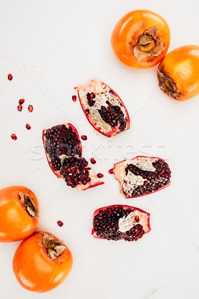 top view of persimmons and pomegranates isolated on white Stock photo © LightFieldStudios