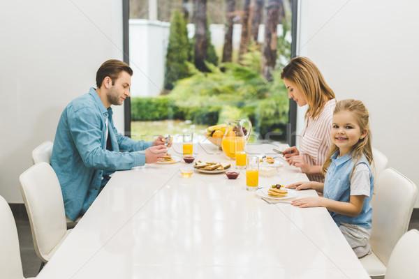 Yandan görünüş ebeveyn küçük kız kahvaltı birlikte Stok fotoğraf © LightFieldStudios