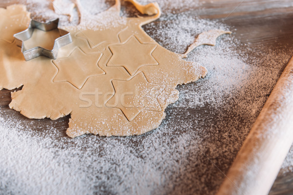 'Close-up view of unbaked cookies with cutter and rolling pin on table  Stock photo © LightFieldStudios