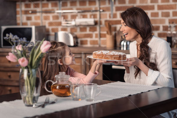 'side view of smiling mother and daughter holding cake in kitchen, mother's day holiday concept Stock photo © LightFieldStudios