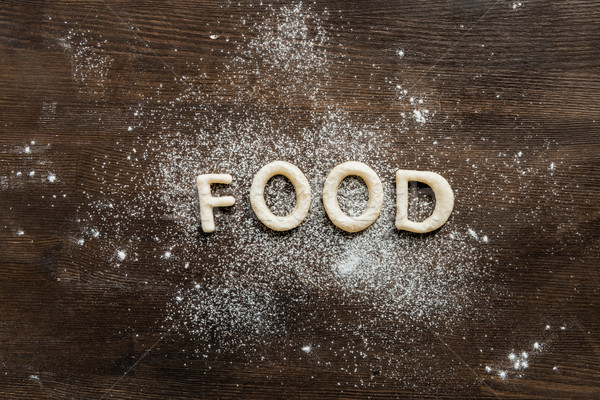 top view of cookies in forms of letters with powdered sugar, cookie dough Stock photo © LightFieldStudios