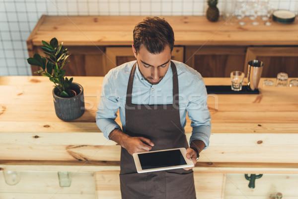 barista using tablet in coffee shop Stock photo © LightFieldStudios