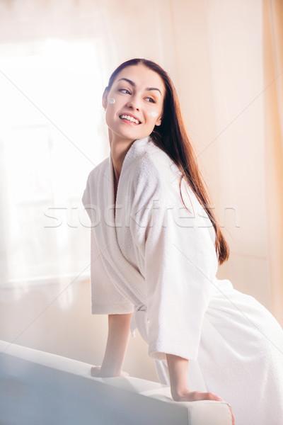 Smiling woman in bathrobe with cream on face Stock photo © LightFieldStudios