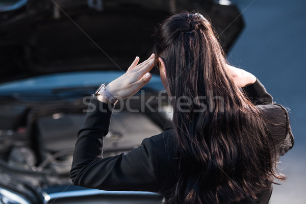 Troubled woman looking at car engine Stock photo © LightFieldStudios