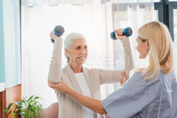 nurse and senior woman with dumbbells Stock photo © LightFieldStudios