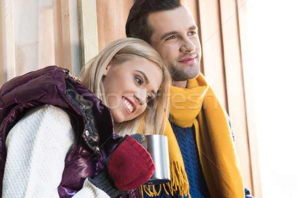 Happy young couple in warm clothes hugging and looking away on porch Stock photo © LightFieldStudios