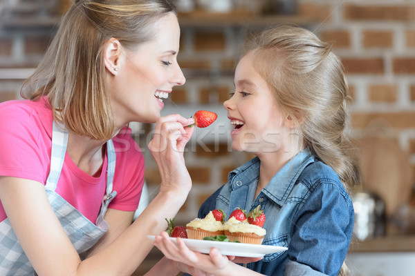 side view of mother feeding daughter with strawberry from cupcake Stock photo © LightFieldStudios