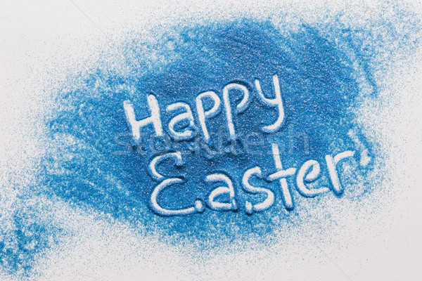 top view of happy easter sign made of blue sand on white surface Stock photo © LightFieldStudios