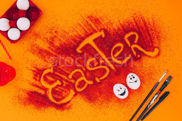 top view of easter sign made of red sand with chicken eggs on orange Stock photo © LightFieldStudios