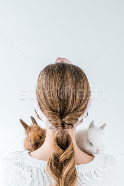 rear view of girl holding adorable furry rabbits isolated on white Stock photo © LightFieldStudios