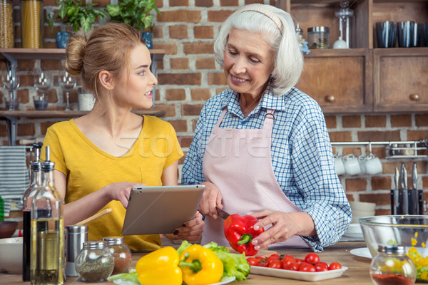 Granddaughter and grandmother cooking together Stock photo © LightFieldStudios