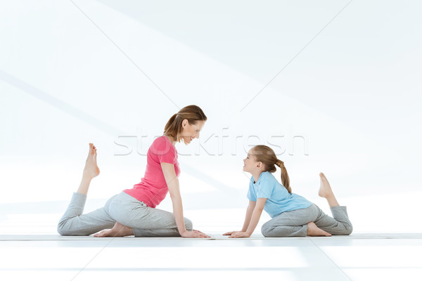 Smiling mother and daughter practicing pigeon yoga pose on mats and looking at each other Stock photo © LightFieldStudios