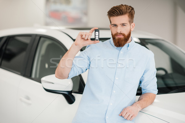 Man holding car key and standing at car in dealership salon    Stock photo © LightFieldStudios