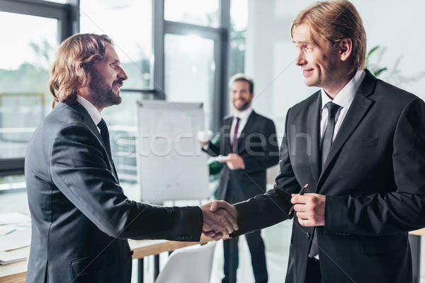 Empresarios apretón de manos vista lateral sonriendo profesional oficina Foto stock © LightFieldStudios