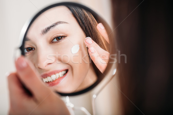 Smiling woman applying face cream Stock photo © LightFieldStudios