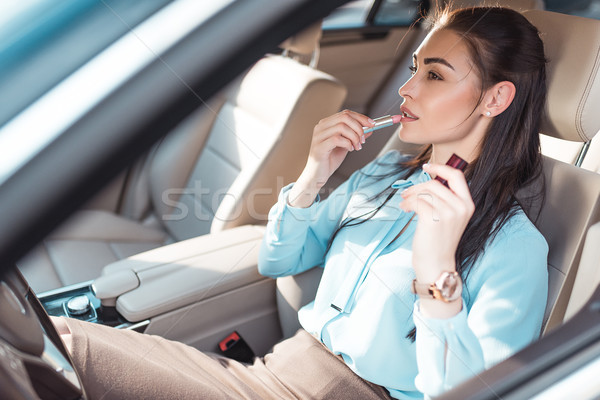 Stock photo: woman applying lipstick in car