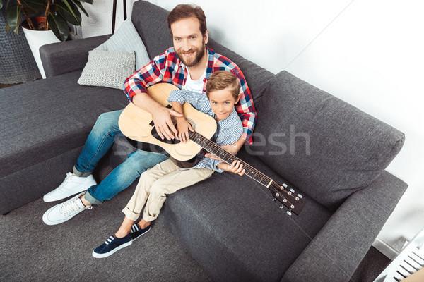 ストックフォト: 父から息子 · 演奏 · ギター · 表示 · 笑みを浮かべて