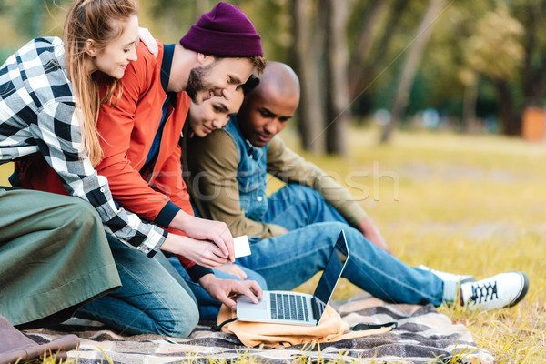 multicultural friends with laptop Stock photo © LightFieldStudios