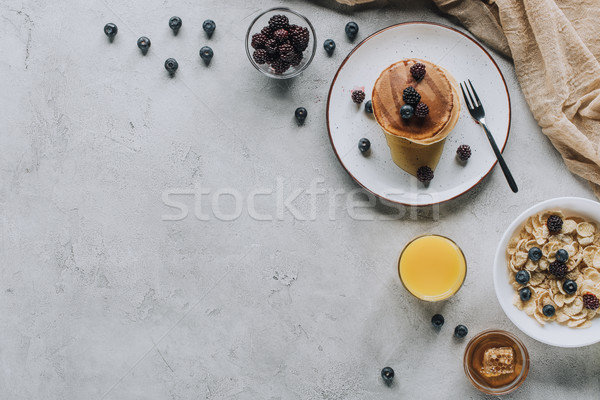top view of tasty healthy breakfast with pancakes, berries, honey and muesli on grey  Stock photo © LightFieldStudios